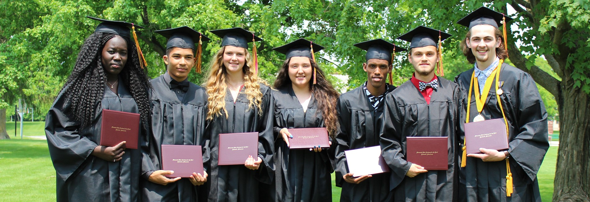 seven high school graduates, wearing graduation caps and gowns, holding their diplomas