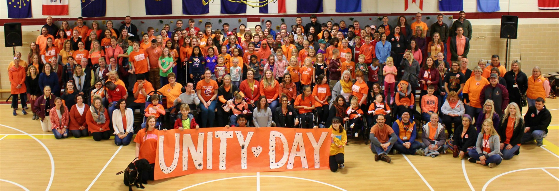Students and staff posing for a large group picture for Unity Day. All are wearing orange and are standing in the MSAB gymnasium.